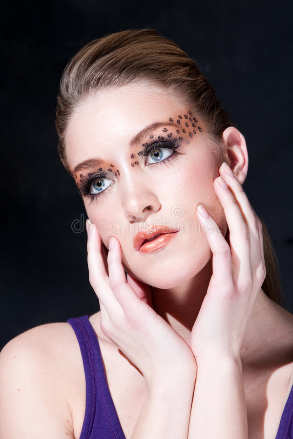 Beatiful face with Leopard print eyes. Tilted face of a beautiful dirty-blond girl with leopard print eyeshadow, isolated royalty free stock photo