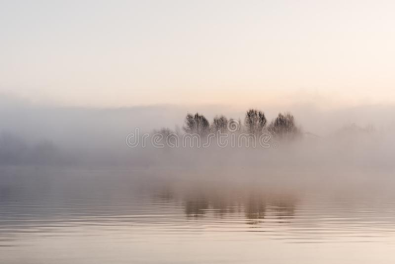 Beatiful Fog winter landscape at lake with tree stock photos