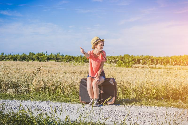 Beatiful girl doing hitchhiking on the road stock images