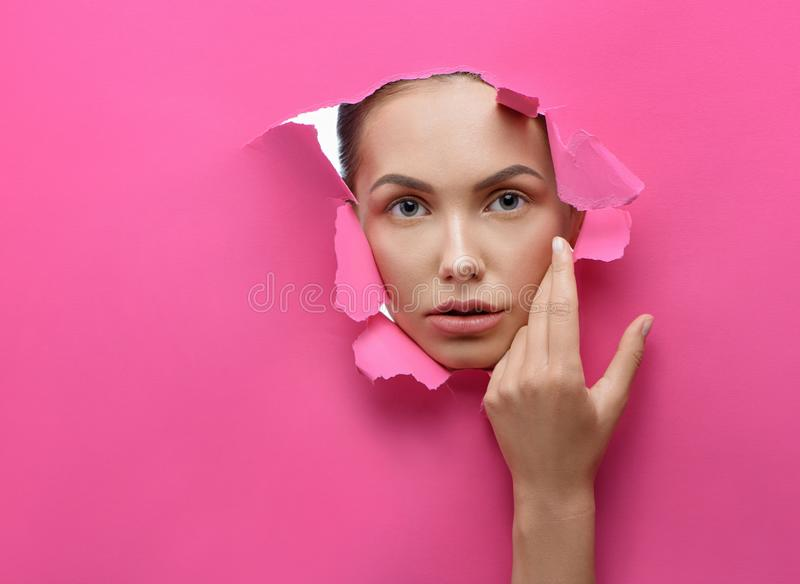 Beatiful girl looking through lacerated hole in stiff pink cardboard. stock image