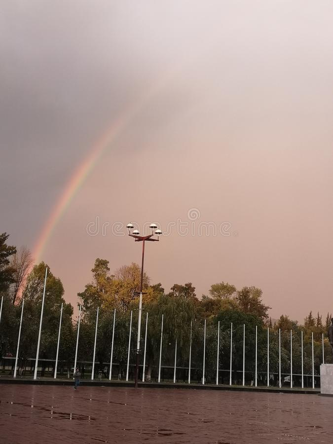 Beatiful rainbow through the clouds royalty free stock photography