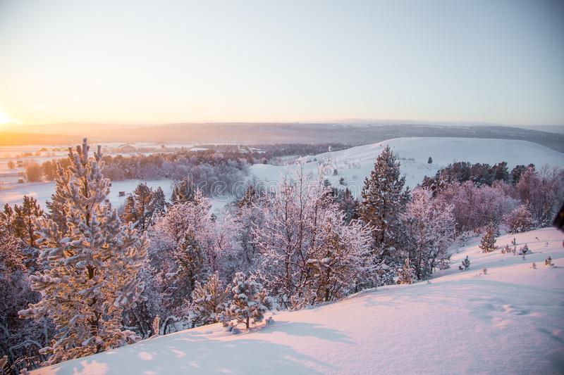 A beatiful sunset landscape of a small Norwegian ton Roros. WInter scenery with an evening sun. Warm, relaxing atmosphere stock images