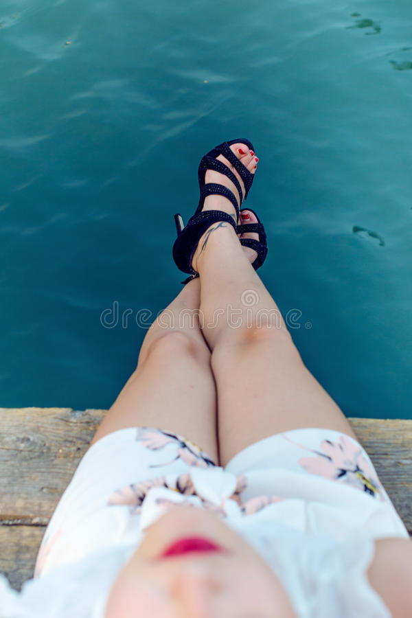 Beatiful woman legs on a natural wooden background with high heeles shoes. Fashion background. Cropped image of pretty young woman stock photos