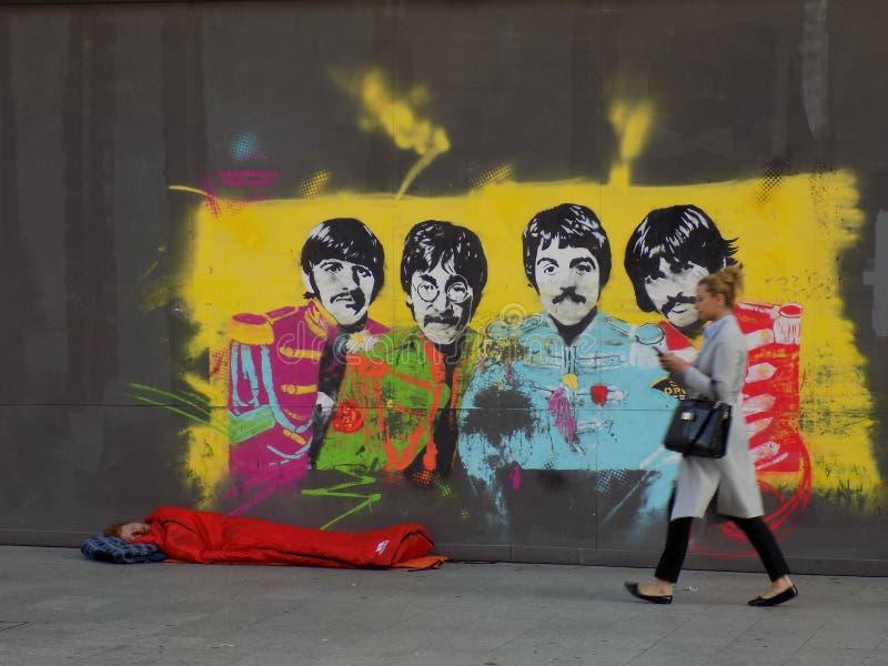Beatles与粗砺的睡眠者的街道艺术 免版税库存照片