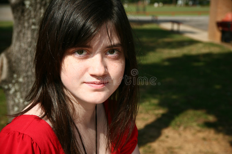 Beatufiul Teen at School. Beautiful 14 year old girl sitting outside at school. Natrual beauty, no make-up or cosmetics royalty free stock photo