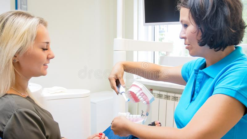 Beatufiul young woman listens to her dentist talking about teeth hygiene stock images