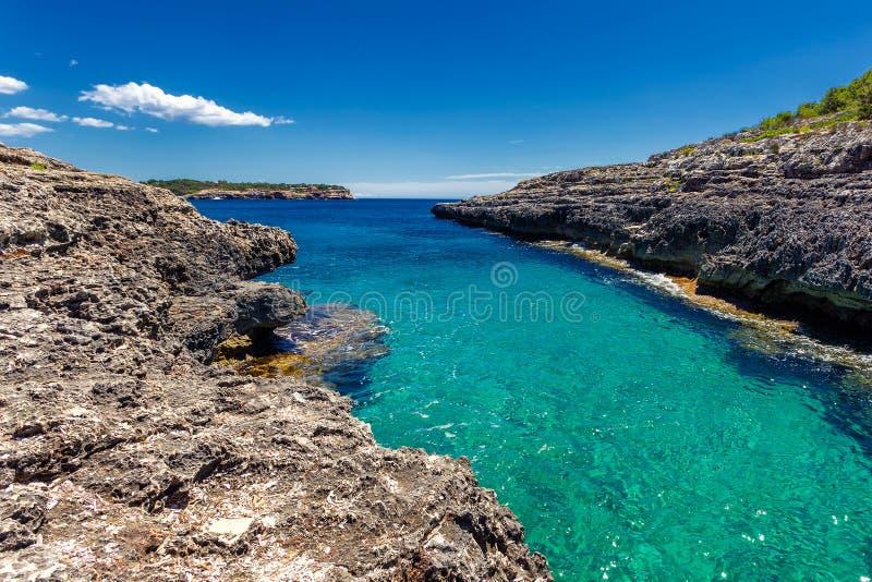 Beatuful在Cala Mondrago国家公园,马略卡使海湾狭窄用清楚的绿松石水 库存图片