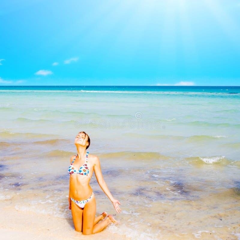 beau agenouillement de fille de plage image libre de droits