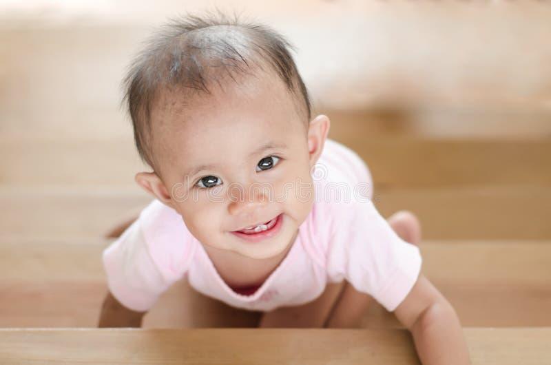 Beau bébé asiatique de sourire tout en rampant vers le haut d'un escalier image libre de droits