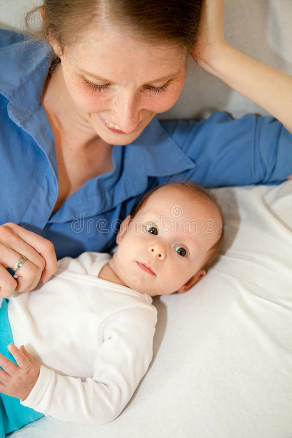Beau bébé avec sa mère se trouvant sur un lit image stock
