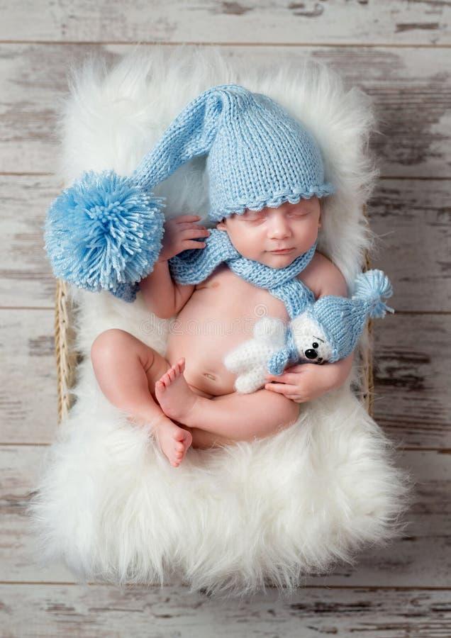 Beau bébé de sommeil dans le chapeau avec le grand pompon sur le berceau pelucheux photo libre de droits