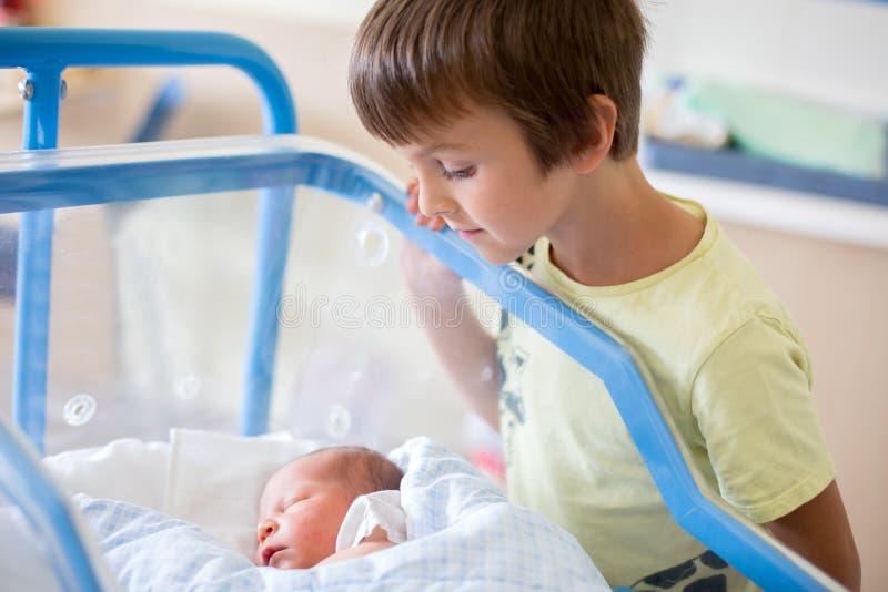 Beau bébé garçon nouveau-né, s'étendant dans la huche dans l'hôpital prénatal, images libres de droits