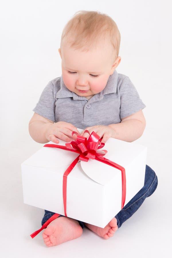 Beau bébé garçon s'asseyant avec le boîte-cadeau au-dessus du blanc photos stock