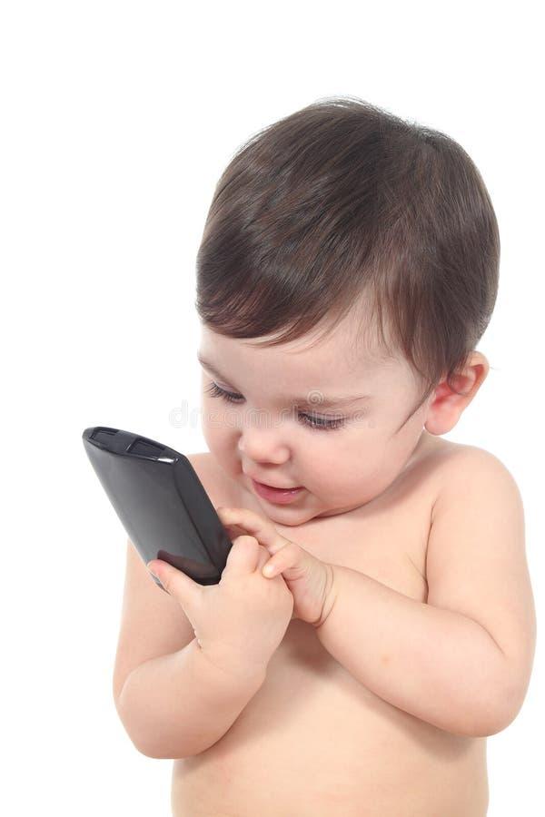 Beau bébé jouant avec un téléphone intelligent image libre de droits