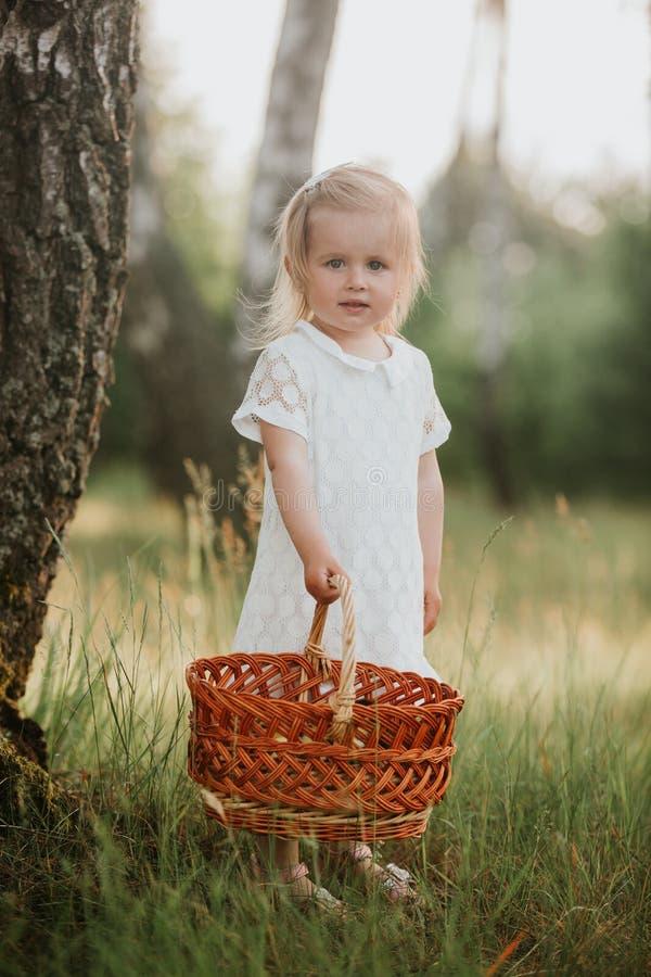 Beau bébé marchant dans un jardin ensoleillé avec un panier peu de fille dans une robe blanche avec un panier en parc photo stock