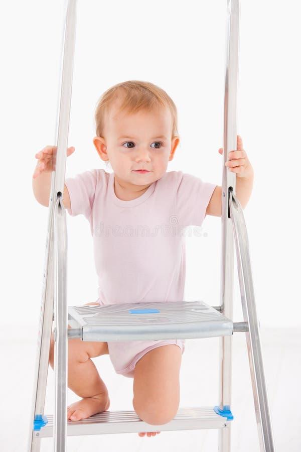 Beau bébé s'élevant sur l'échelle photo stock