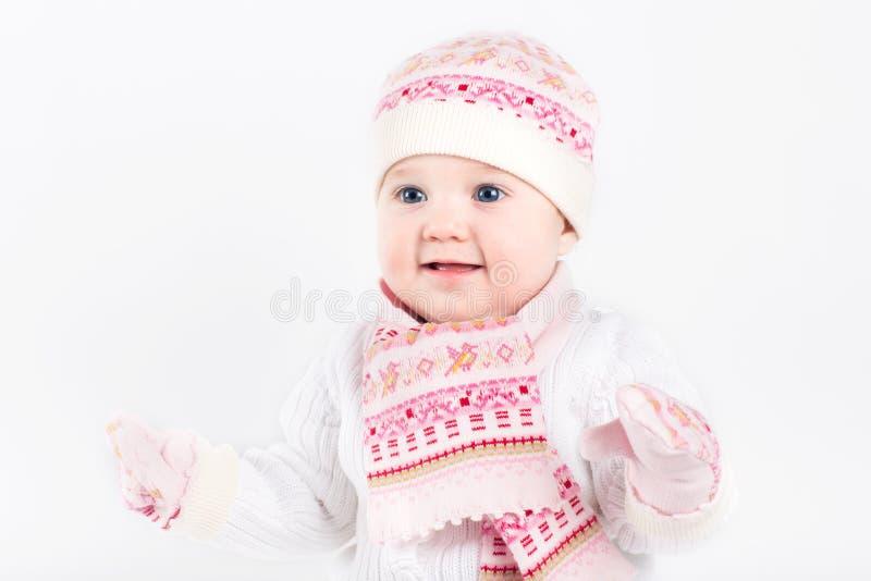 Beau bébé utilisant le chapeau, l'écharpe et les mitaines tricotés image stock