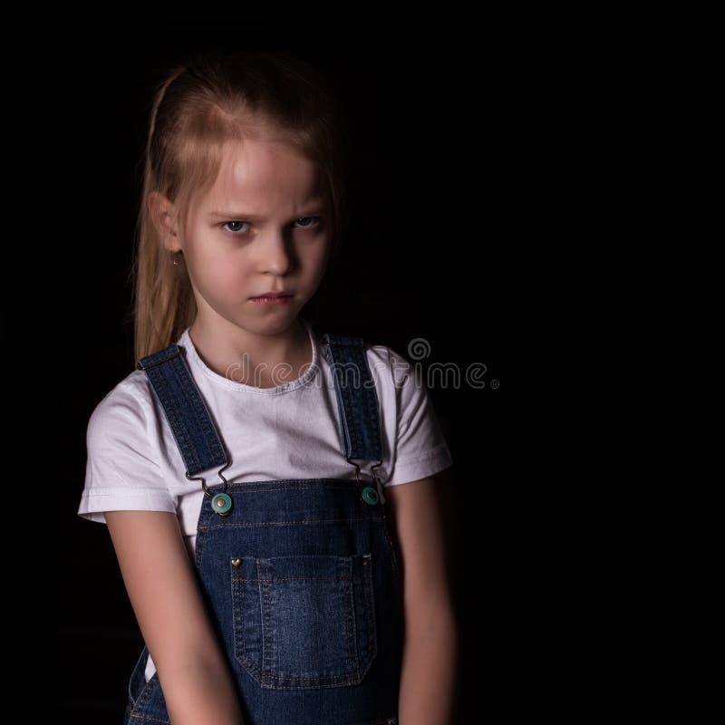 Beau blond petite fille sur un fond fonc? Elle se tient dans diff?rentes poses et montre diff?rentes ?motions libre photo stock