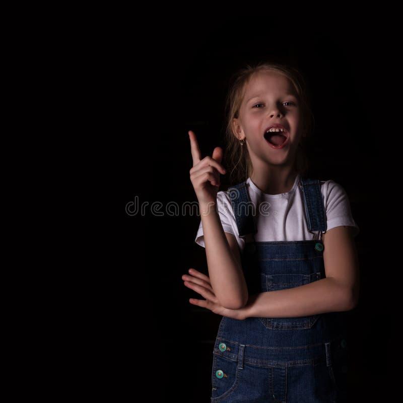 Beau blond petite fille sur un fond fonc? Elle se tient dans diff?rentes poses et montre diff?rentes ?motions libre images libres de droits