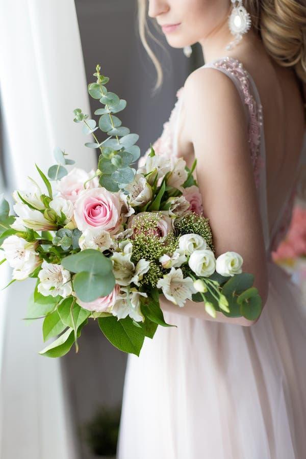 Beau bouquet élégant des roses et de la verdure dans les mains douces de la belle fille de jeune mariée dans une robe rose l'air images stock