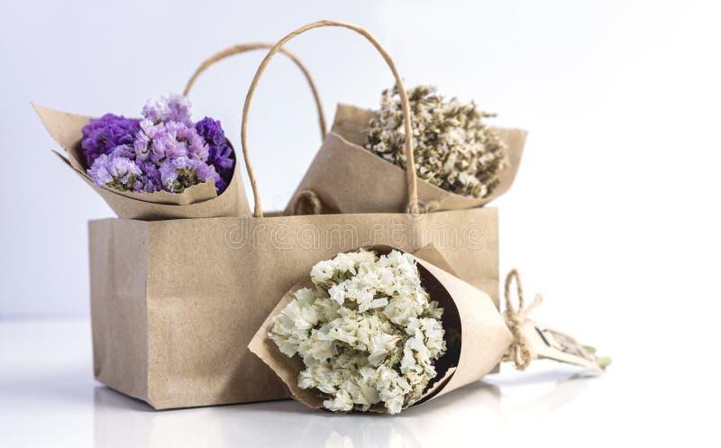 Beau bouquet de fleurs séchées enveloppé de papier Kraft dans un sac en papier image libre de droits