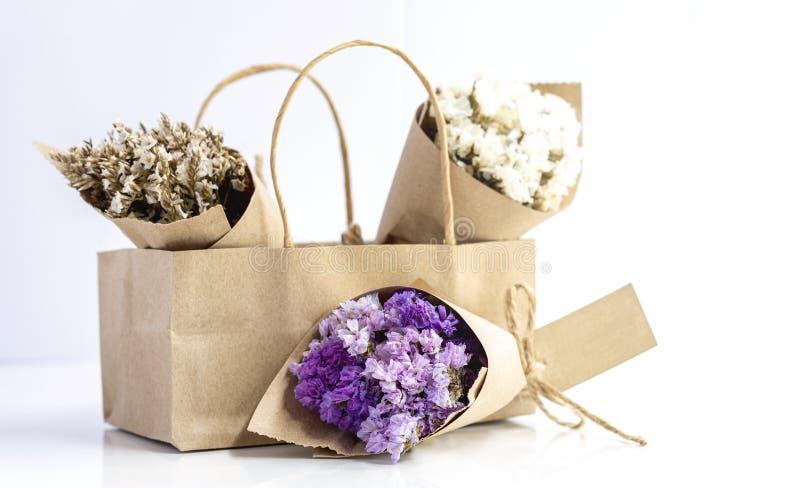 Beau bouquet de fleurs séchées enveloppé de papier Kraft dans un sac en papier photo stock