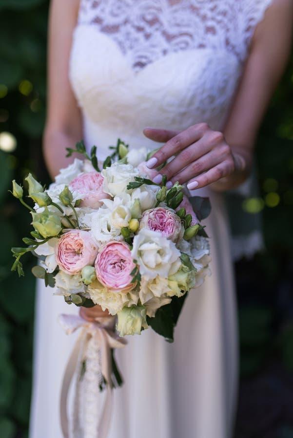 Beau bouquet de mariage dans des mains de la jeune mariée Fleurs à la mode et modernes de mariage Femme dans la robe de mariage d images libres de droits