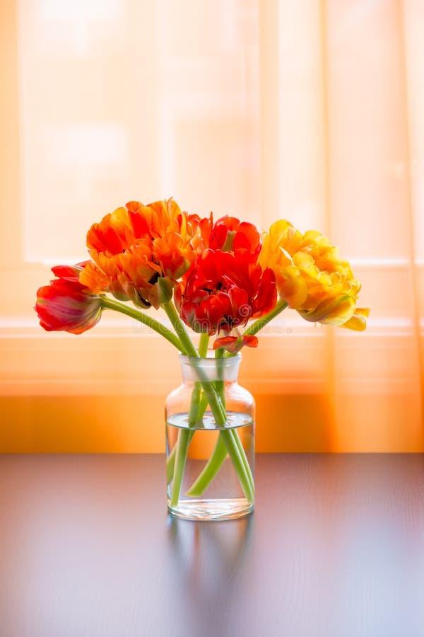 Beau bouquet de tulipes dans le vase sur la table près de la fenêtre photos stock