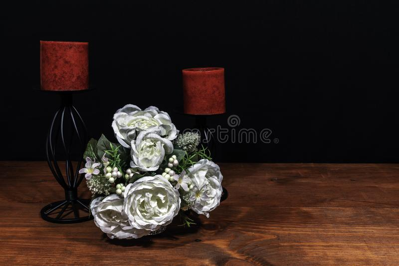 Beau bouquet des bougies rouges disposées de fleurs sur un support sur une table en bois images libres de droits