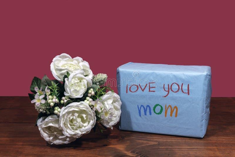 """Beau bouquet des fleurs disposées et un présent avec un message """"amour vous maman """"sur une table en bois image libre de droits"""