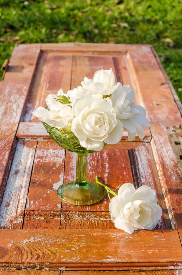 Beau bouquet des roses avec des baisses dans le vase en verre vert sur la vieille table en bois photos stock