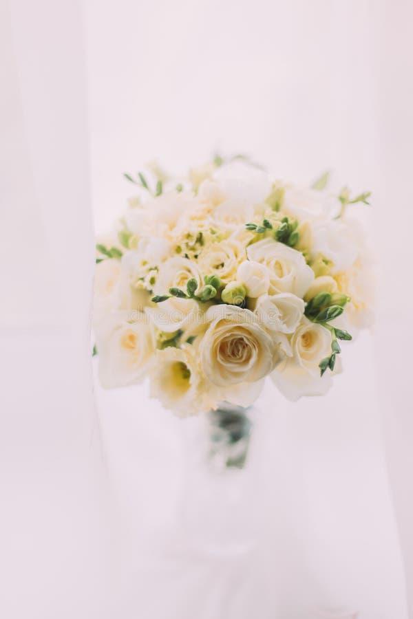 Beau bouquet des roses dans le vase à verre taillé sur le fond lumineux photo stock