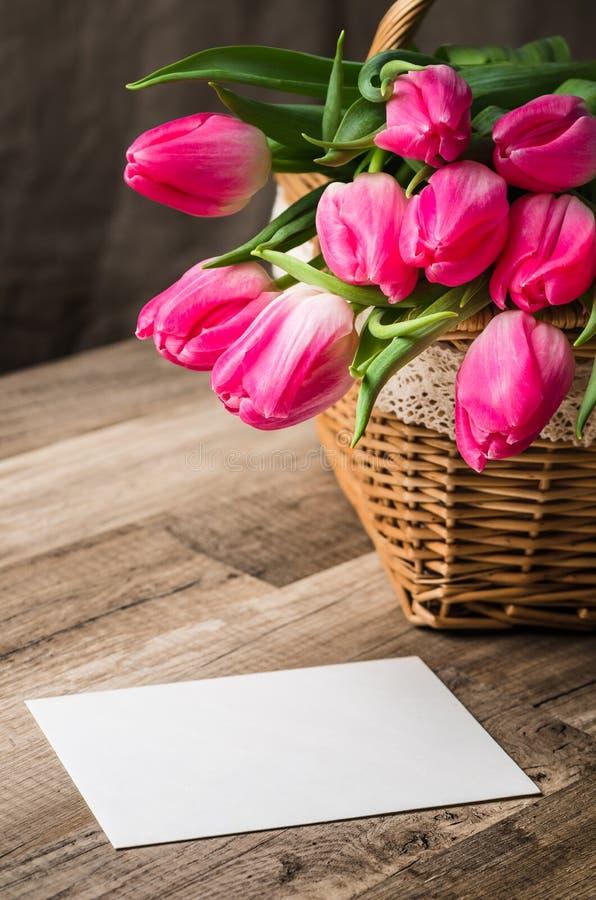 Beau bouquet des tulipes roses et des félicitations sur le tabl photographie stock