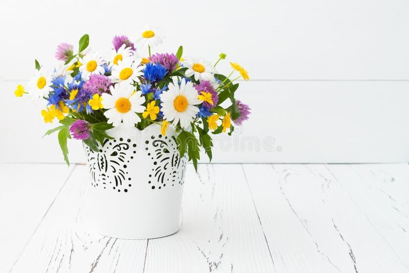 Beau bouquet des wildflowers lumineux dans le panier au-dessus de la vieille table rustique Concept de carte de voeux de jour de  image libre de droits