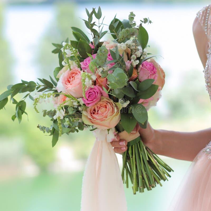 Beau bouquet nuptiale dans des mains de la jeune mariée Épouser le bouquet des roses de pêche par David Austin, aqua rose rose tê photos libres de droits