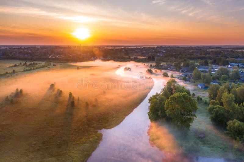 Beau brouillard moulu au-dessus d'une petite rivière parmi les prés herbeux dans les zones rurales, tôt le matin à l'aube image stock