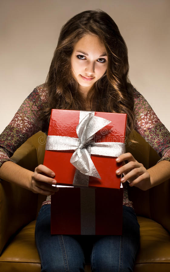 Beau brunette jetant un coup d'oeil le cadre de cadeau intérieur. image libre de droits