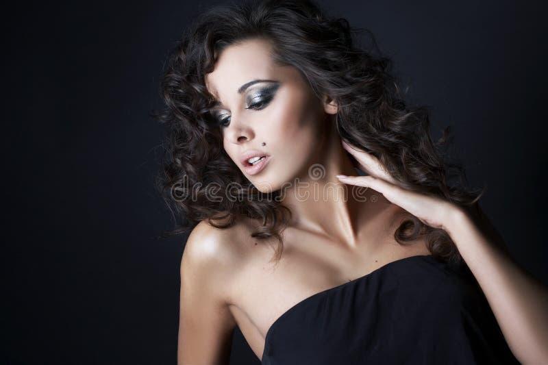 Beau brunette posant sur le fond noir photo libre de droits