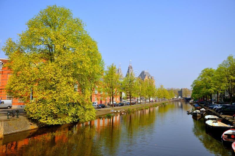 Beau canal de rivière avec des bateaux et des arbres verts à Amsterdam, Holland Netherlands image libre de droits
