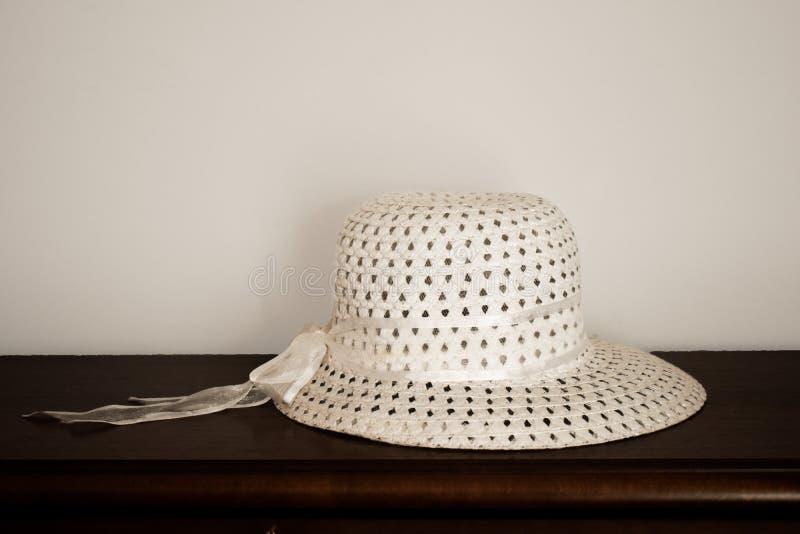 Beau chapeau élégant d'été sur la table en bois foncée avec le fond blanc Chapeau de soleil de femme élégante photos stock