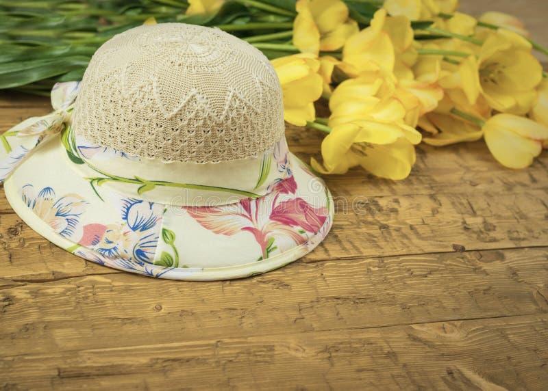 Beau chapeau d'été et un bouquet des tulipes jaunes sur une table en bois images stock