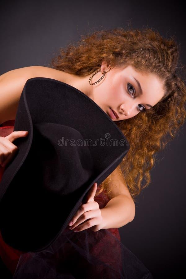Beau chapeau red-haired de fixation de fille photo stock