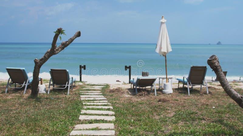 Beau chemin des pierres à la plage d'océan avec des parapluies et des lits pliants image stock