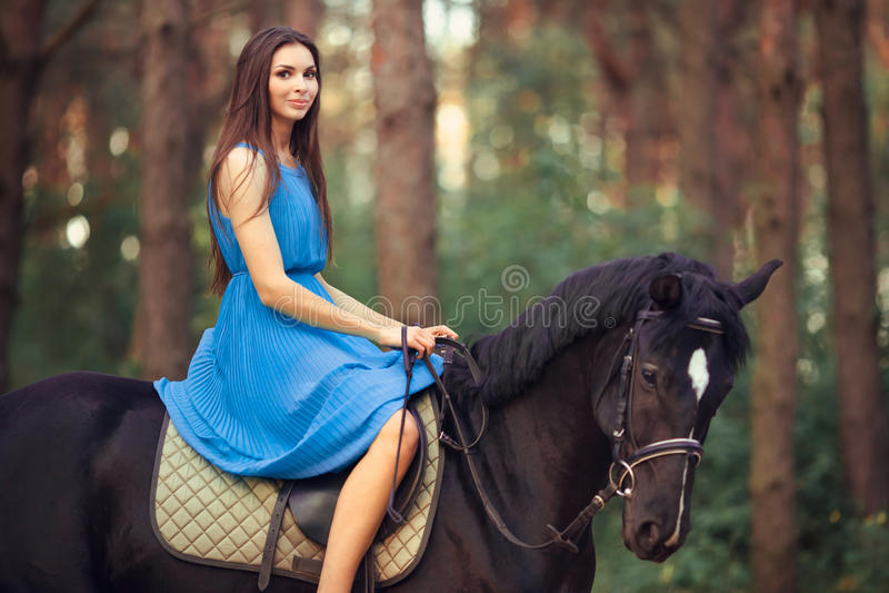 Beau cheval d'équitation de femme dans la forêt photo stock