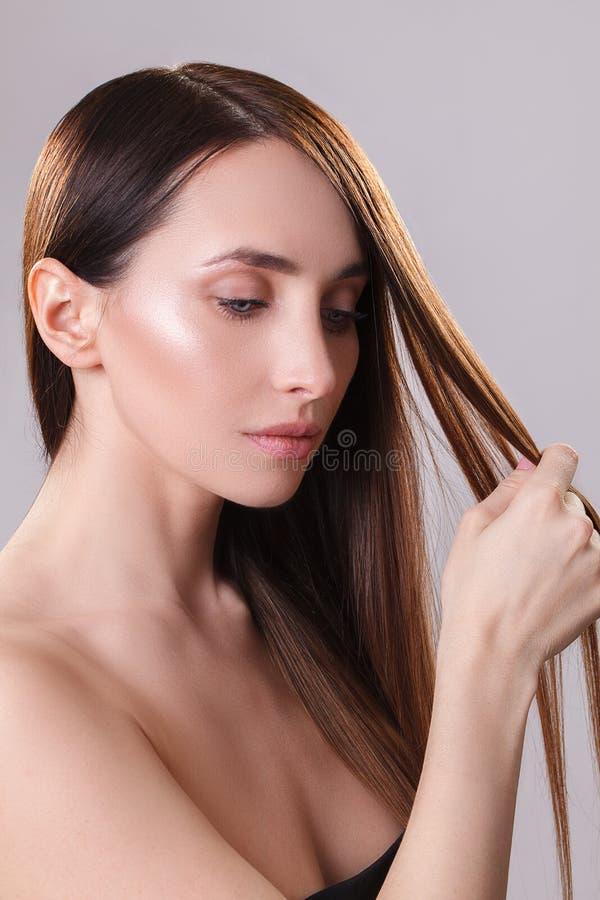 Beau cheveu Femme de brune de beauté avec de longs cheveux luxueux et yeux fermés au-dessus de fond bleu Maquillage Modèle de fil photographie stock libre de droits