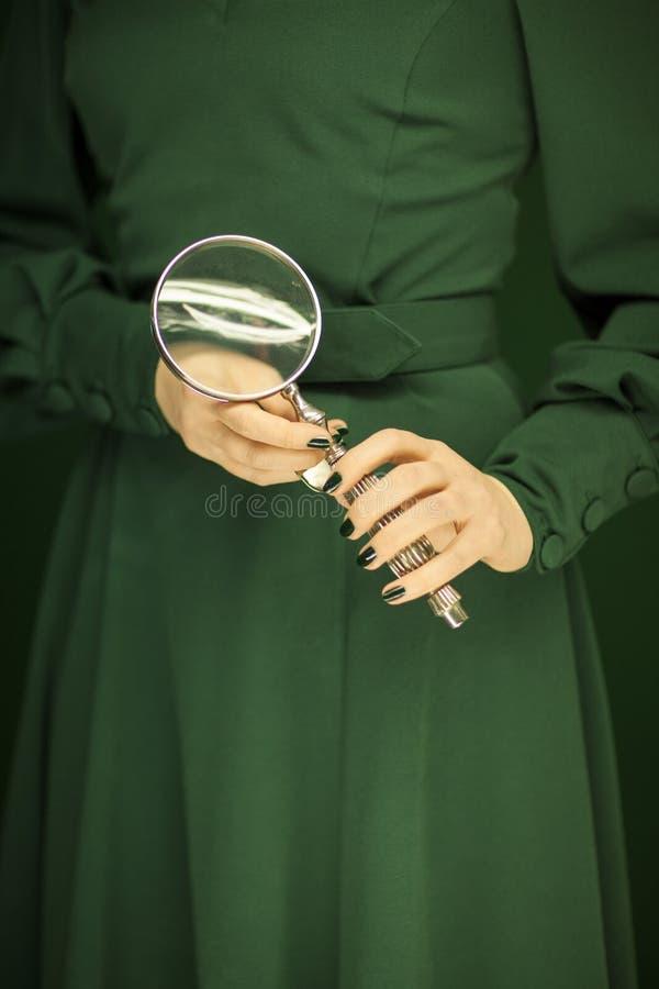 Beau chiffre de femme dans la robe verte avec le fond vert tenant la loupe de vintage photos libres de droits