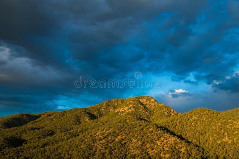 Beau ciel égalisant au-dessus d'une crête de montagne plaquée dans une forêt de genévrier et de pin photographie stock