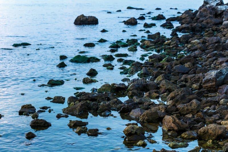 Beau ciel bleu et plage en pierre avant coucher du soleil sur la mer photos libres de droits