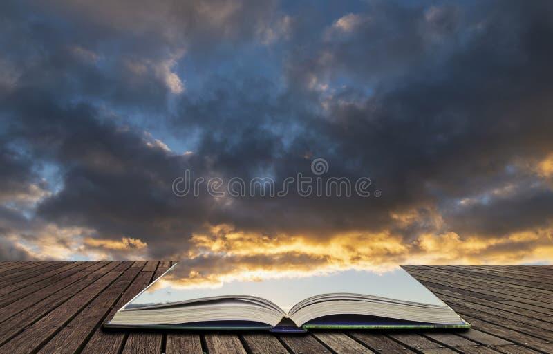 Beau ciel d'or vibrant coloré de coucher du soleil d'heure avec la formation de nuage et coucher de soleil en pages de livre ouve photos stock