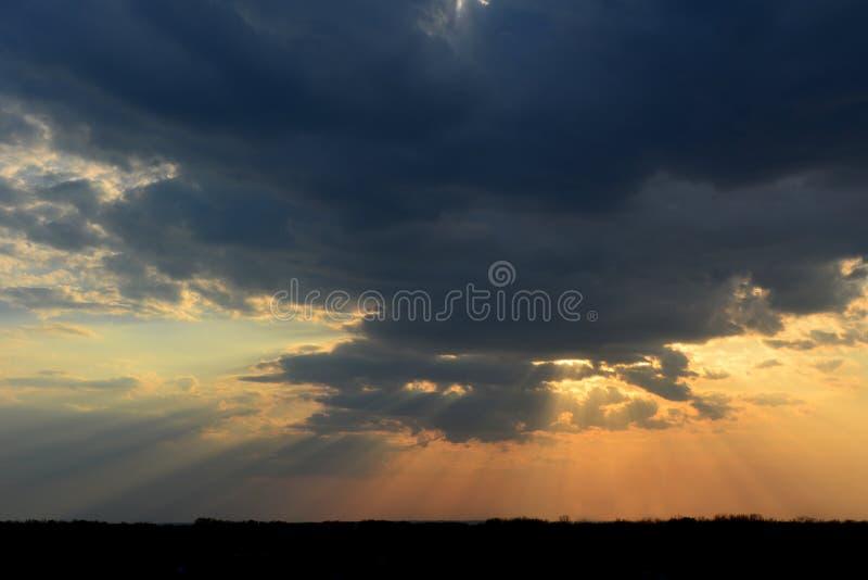 Beau ciel de coucher du soleil avec la lumière dramatique Rayons de Sun par les nuages foncés photo stock